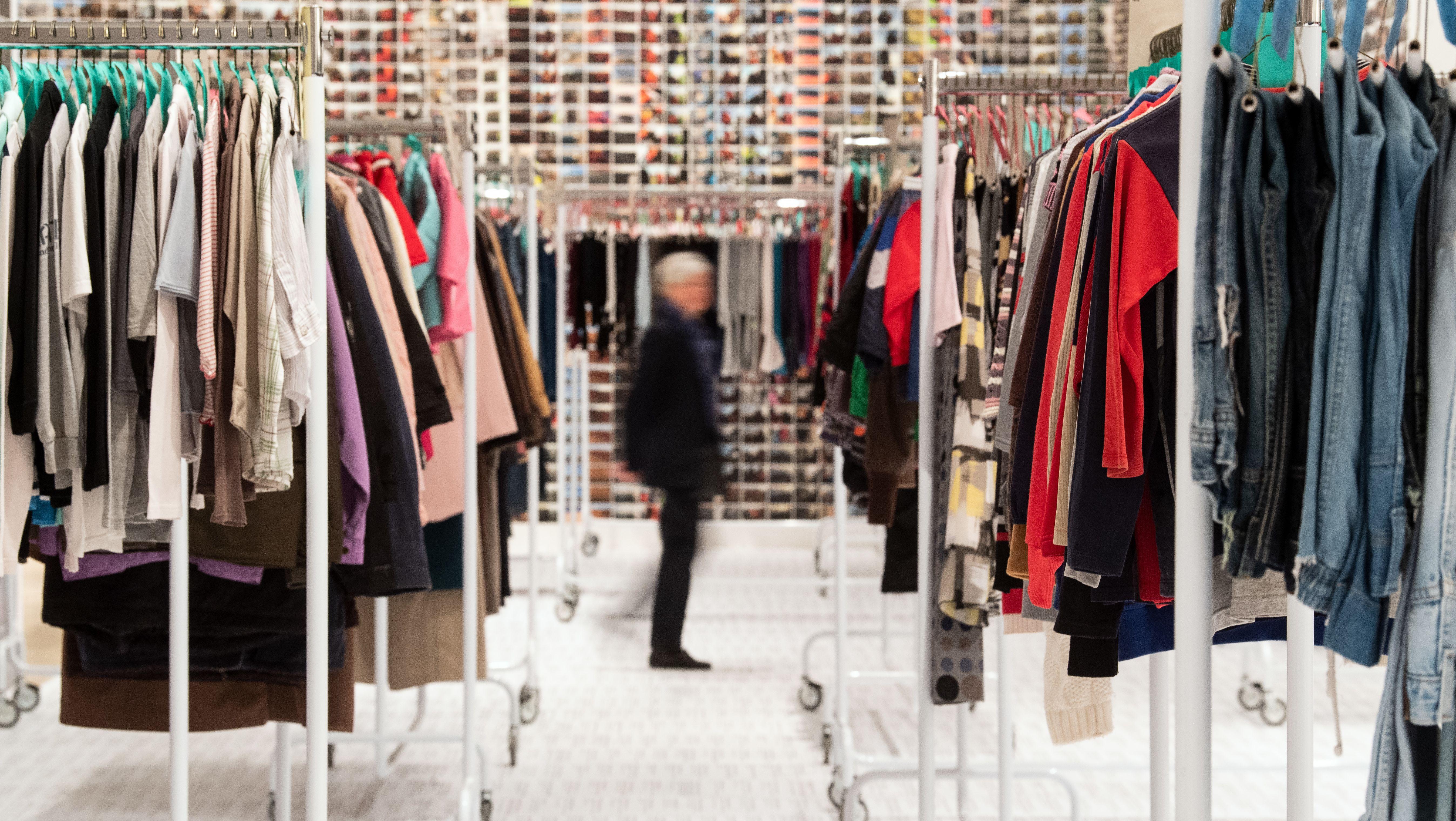 """Ein Besucher geht durch die Installation """"Laundromat"""" des chinesischen Künstler Ai Weiwei aus dem Jahr 2012  - zu sehen ist eine bunte Aneinanderreihung von Hemden, Jacken und Hosen, die an Kleiderständern hängt"""