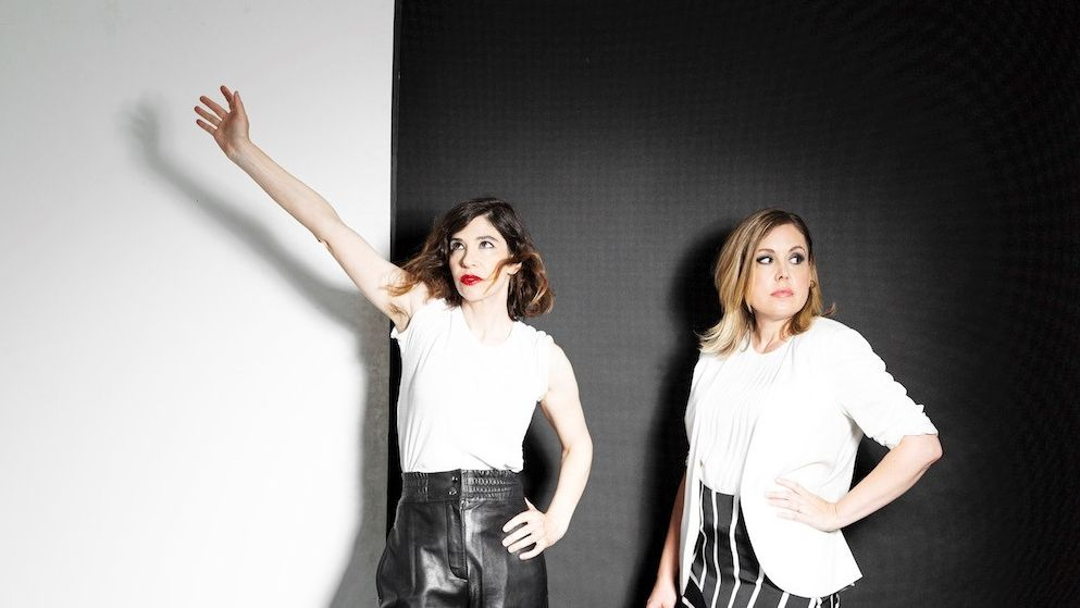 Zwei Frauen stehen vor einer schwarzen Wand.