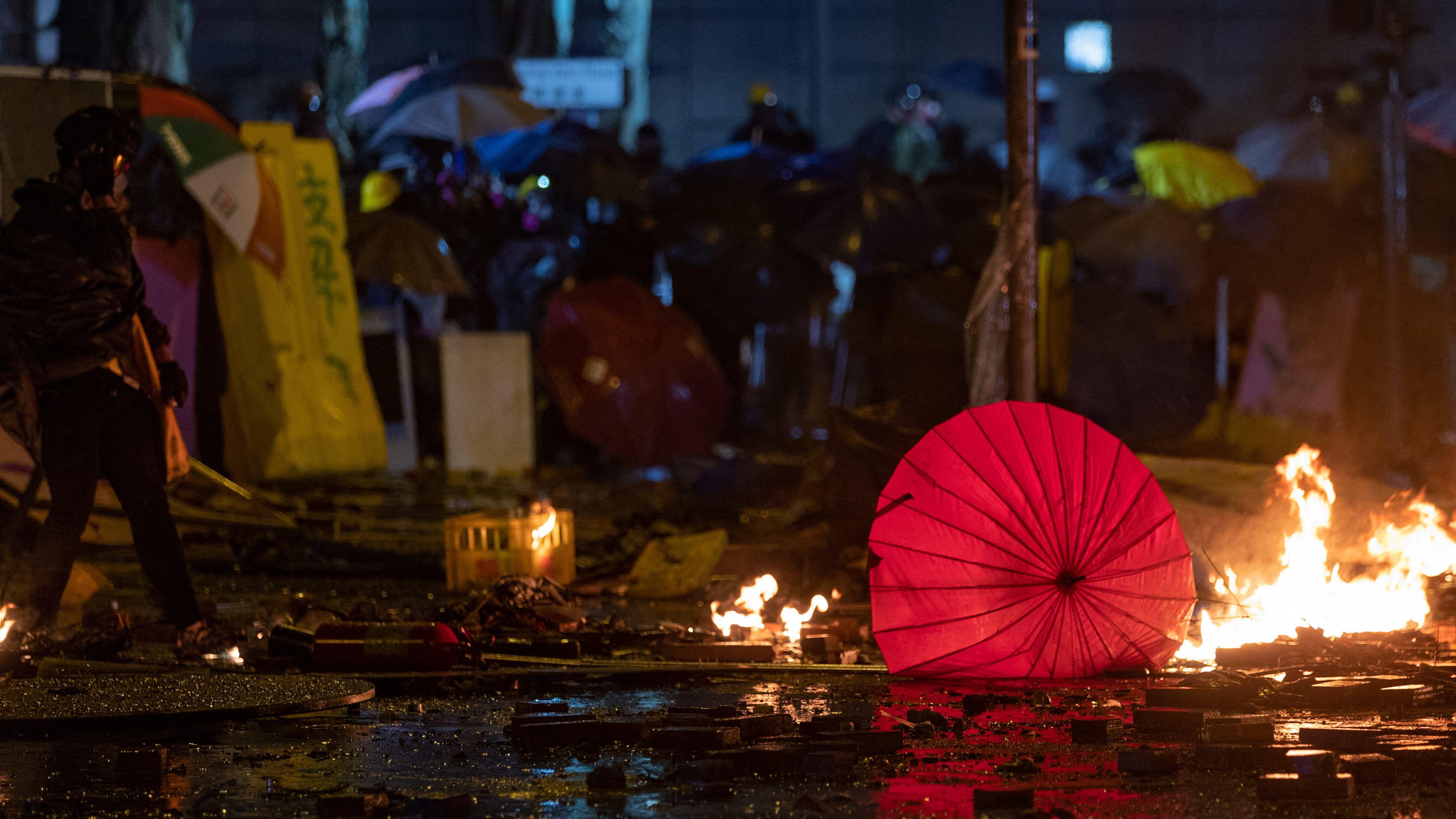 Proteste in Hongkong: Ein roter Schirm liegt auf nasser Straße, kleinere Feuer am Boden