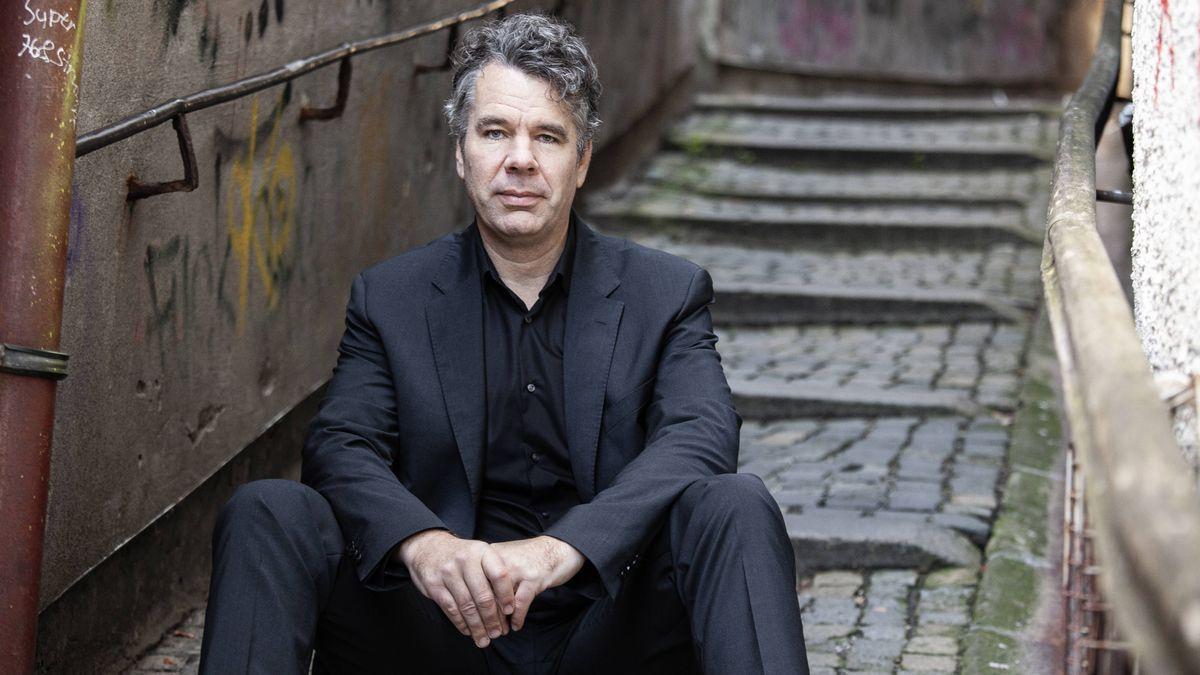Ein Mann sitzt im Anzug auf einer Treppe und schaut in die Kamera
