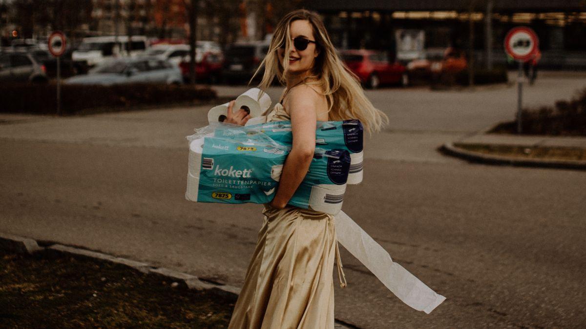 Frau im goldenen Ballkleid mit Klopapier auf einem Supermarkt Parkplatz