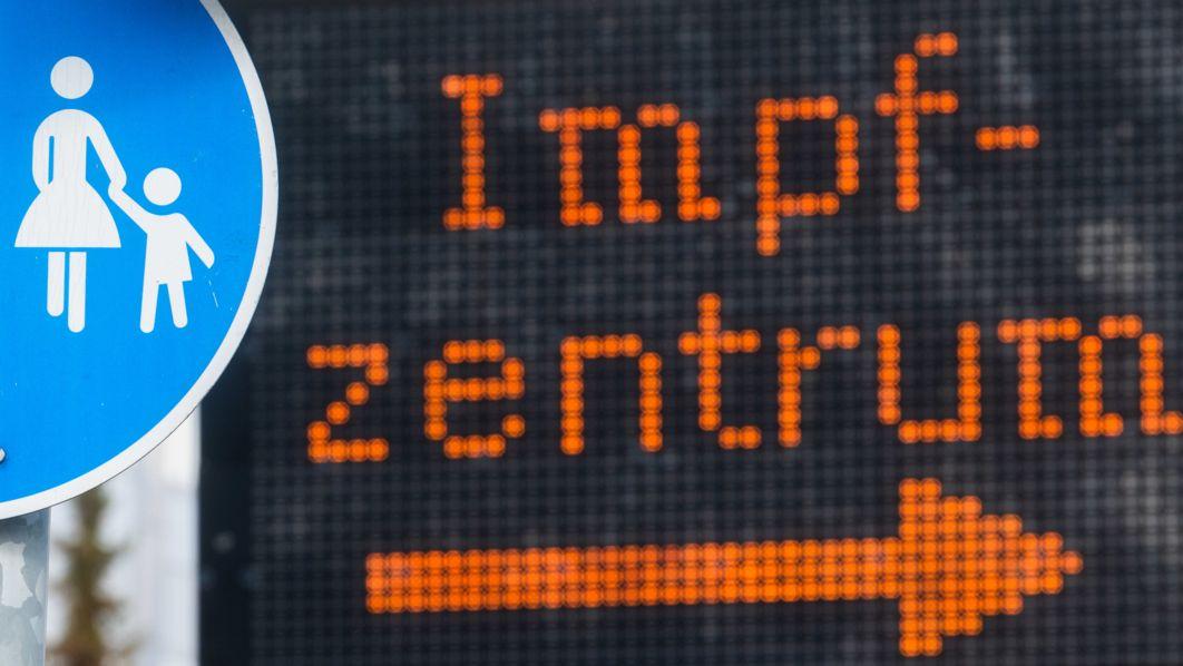 """Eine elektronische Anzeigetafel mit dem Wort """"Impfzentrum"""" hinter einem Verkehrsschild """"Sonderweg Fußgänger"""" weist den Weg zu einem Impfzentrum."""