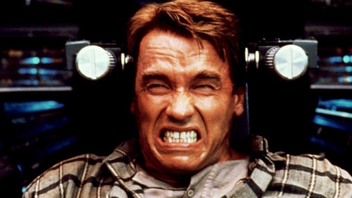"""Arnold Schwarzenegger sitzt mit verzerrtem Blick in einem Sitz (Filmstill aus """"Total Recall"""", 1990)"""
