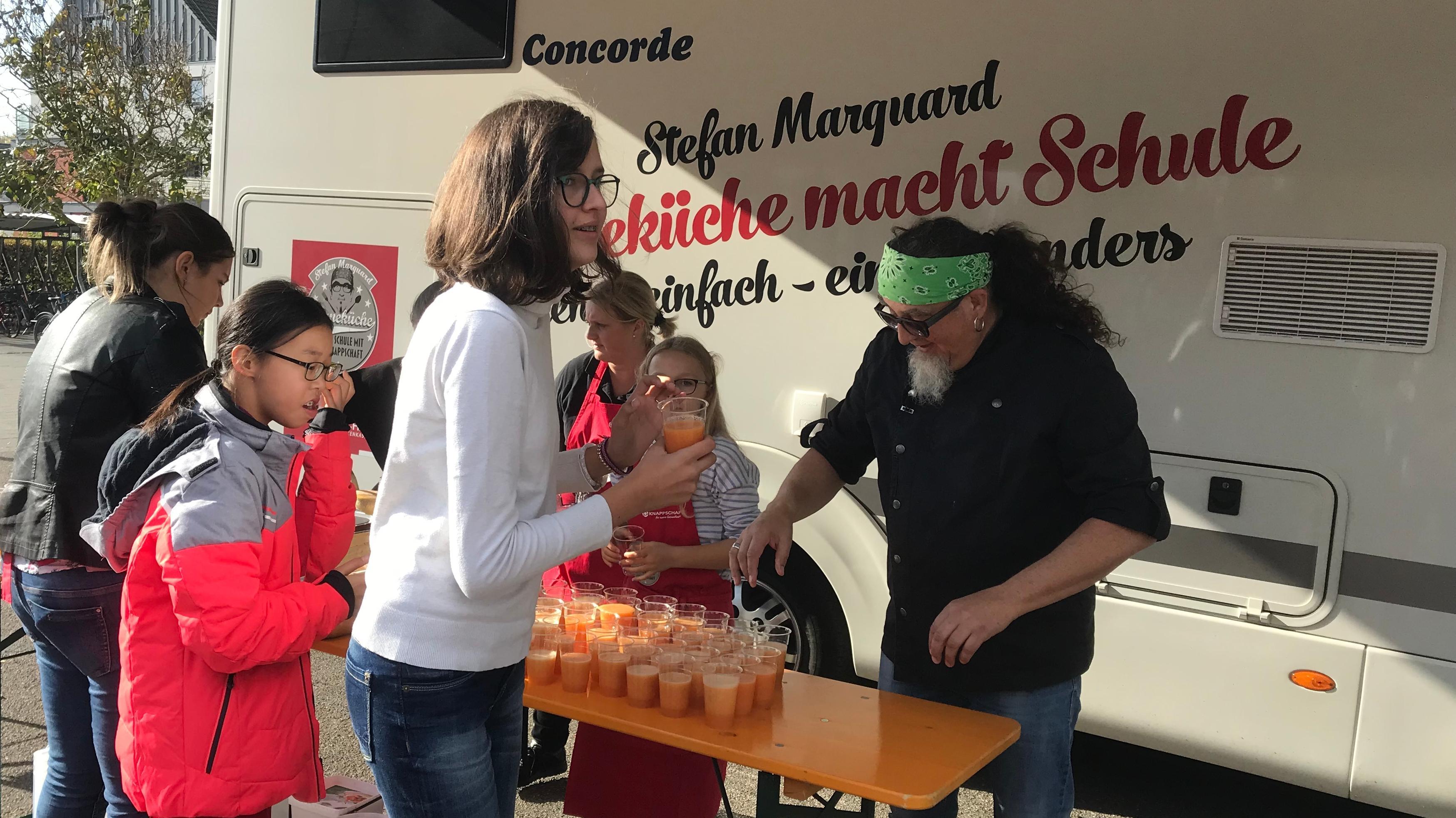 Sternekoch Stefan Marquard steht mit einen grünen Stirnband im Haar hinter einem Biertisch und schenkt Smoothies an Schüler aus.