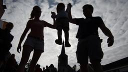 Familie vor einer Kirche: Mutter und Vater heben ihr Kleinkind in die Luft. | Bild:picture alliance/Friso Gentsch/dpa