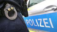 Symbolbild: Handschellen und Polizeiauto | Bild:dpa-Bildfunk/Karl-Josef Hildenbrand