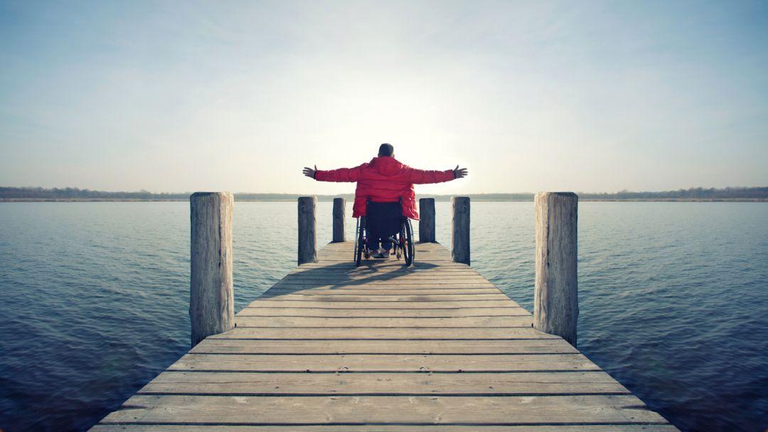 Ein Rollstuhlfahrer steht auf einem Steg an einem See (Symbolbild)