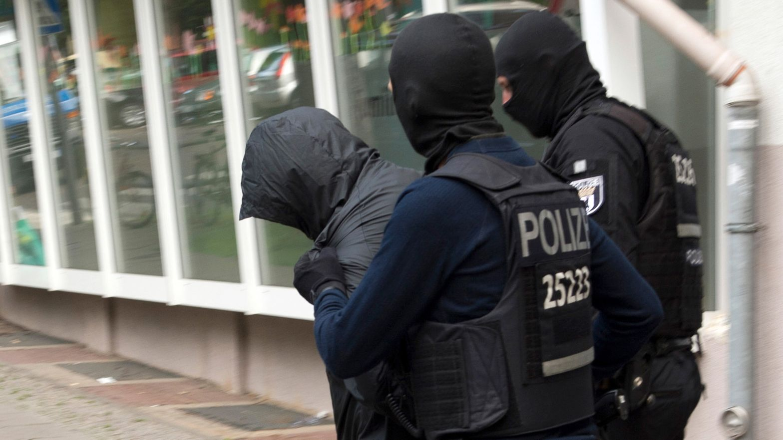 Polizeibeamte führen einen Mann ab. Dreieinhalb Monate nach dem spektakulären Diebstahl einer 100-Kilo-Goldmünze aus dem Berliner Bode-Museum im März 2017 hat die Polizei zwei Verdächtige festgenommen.