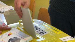 Jemand steckt einen Wahlzettel in eine knallgelbe Wahlurne | Bild:BR/Gisela Staiger