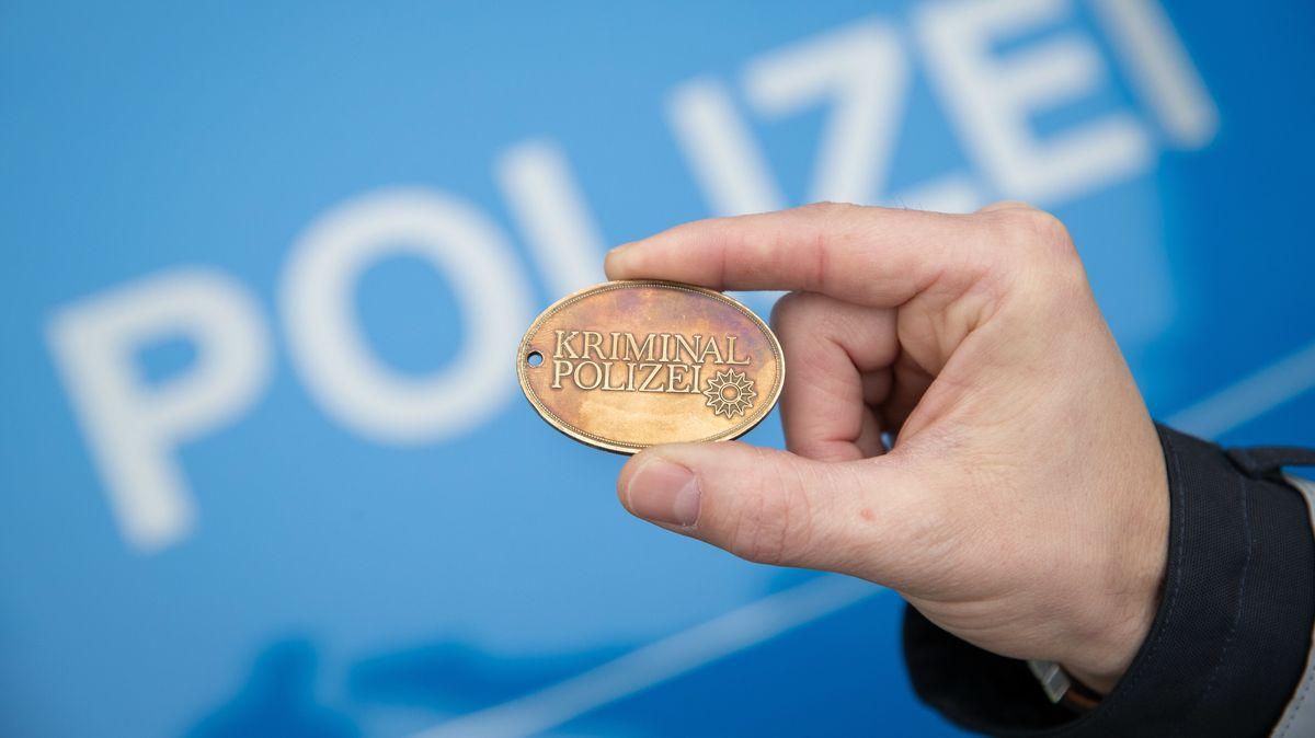 Ein Polizist hält eine Dienstmarke der Kriminalpolizei in seiner Hand. Dienstmarken, aber auch Dienstausweise, können Polizisten dadurch identifizieren, dass sie eine bestimmte Dienstnummer tragen.