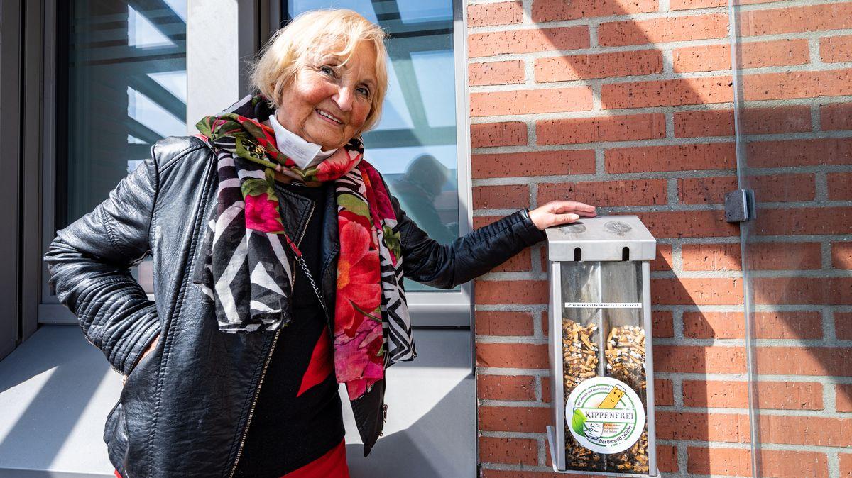 """Karin Meixner-Nentwig, von dem Verein """"Amberger Kippenjäger"""" steht neben einem Sammelbehälter mit Zigarettenkippen."""