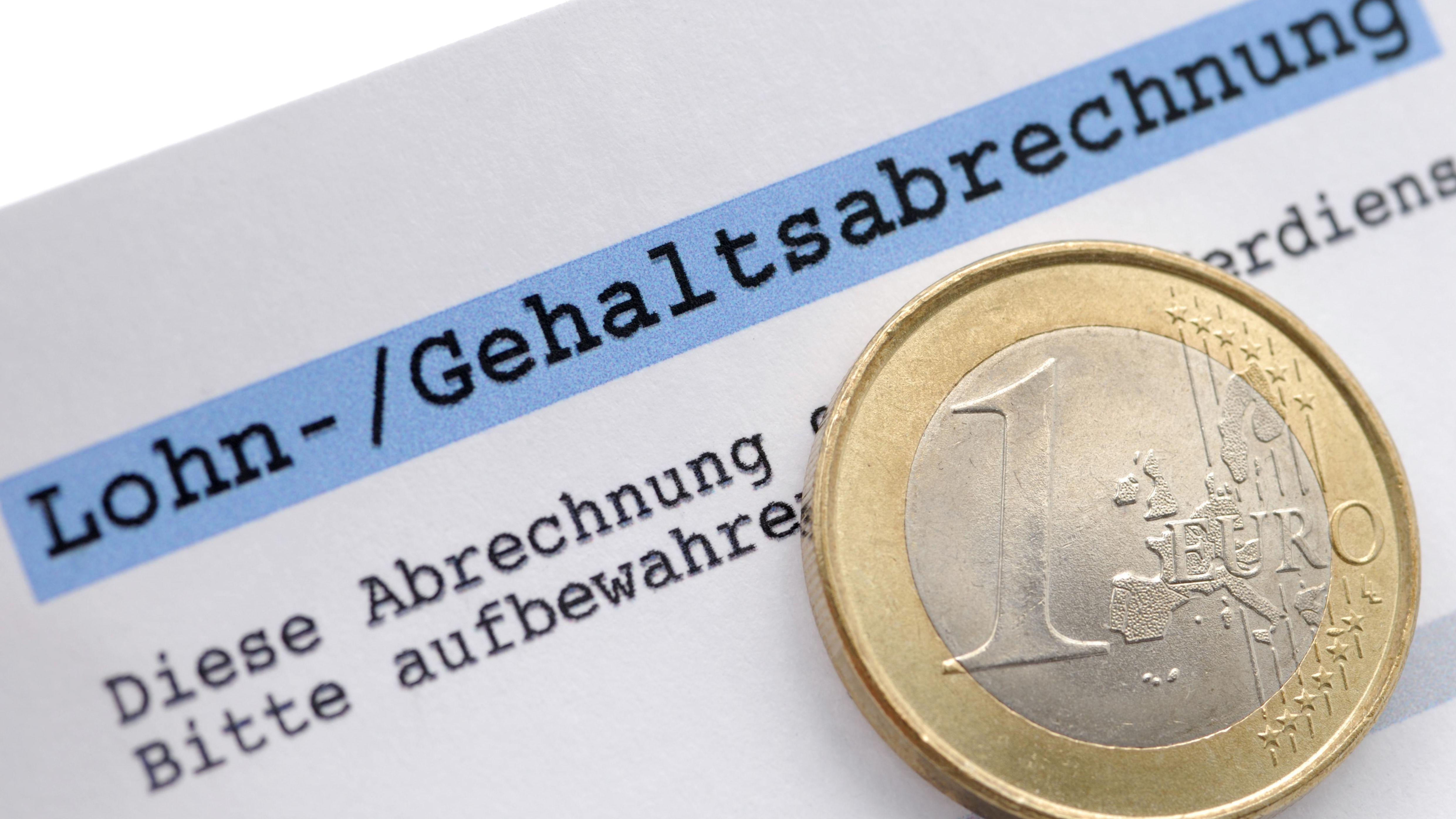 Eine Gehaltsabrechnung liegt neben einer Euromünze, Symbolbild.