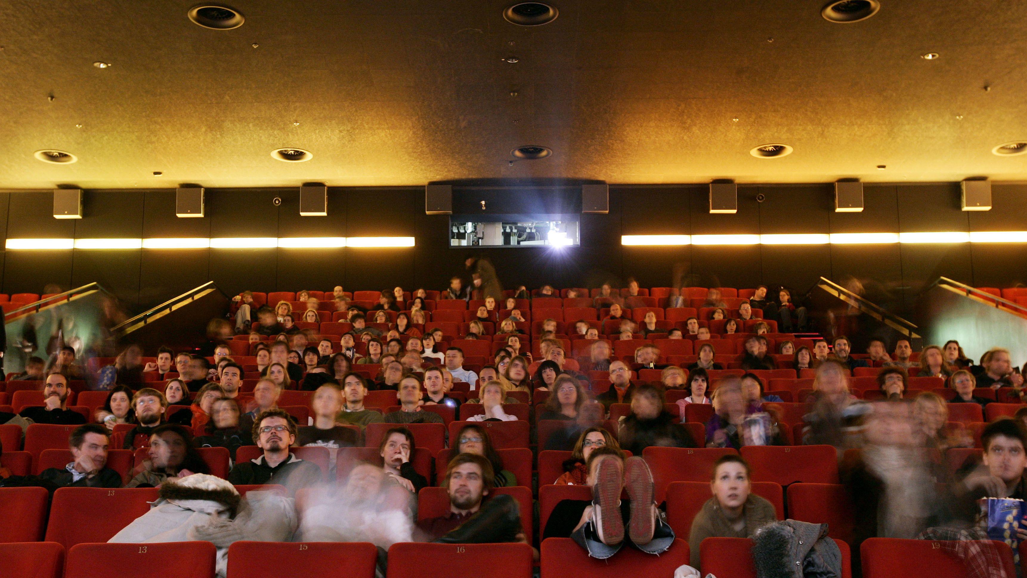 Voller Kinosaal: Mehrere Besucher schauen auf eine Kino-Leinwand