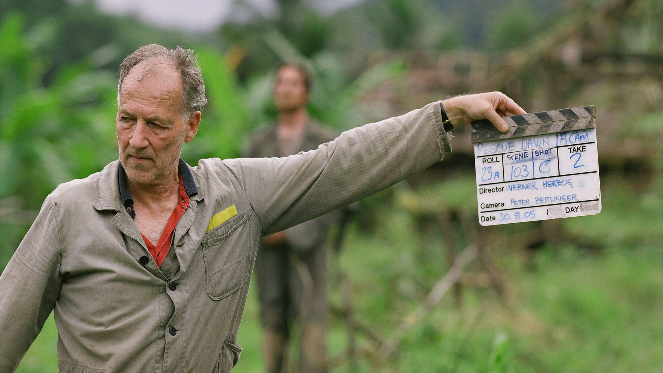 """Werner Herzog steht am Set von """"Rescue Dawn"""" und hält in seiner linken Hand eine Filmklappe."""
