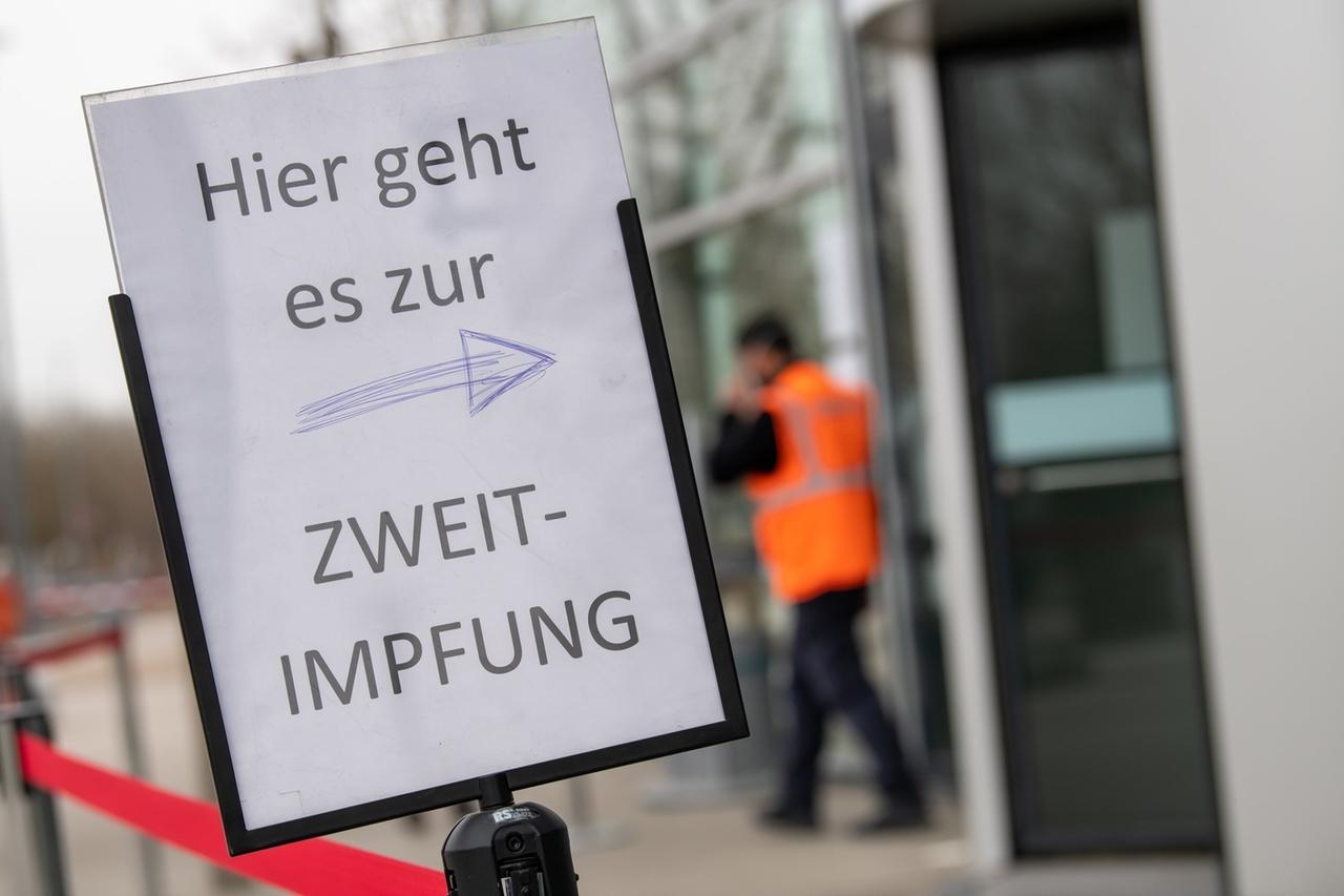 """04.03.2021, Bayern, München: """"Hier geht es zur Zweit-Impfung"""" steht auf einem Schild am Eingangsbereich zum Gelände der Messe München. Foto: Peter Kneffel/dpa +++ dpa-Bildfunk +++"""