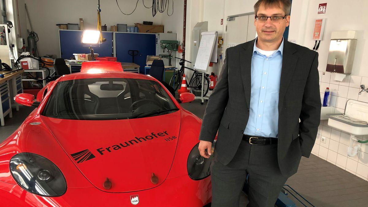 Ein Mann steht vor einem roten Auto