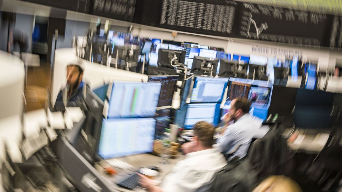 Börsenhändler sitzen im Handelssaal der Börse in Frankfurt an ihren Monitoren