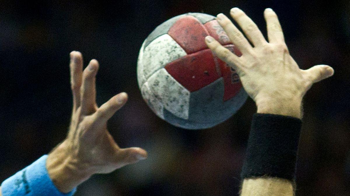 Zwei Hände greifen nach einem Handball.