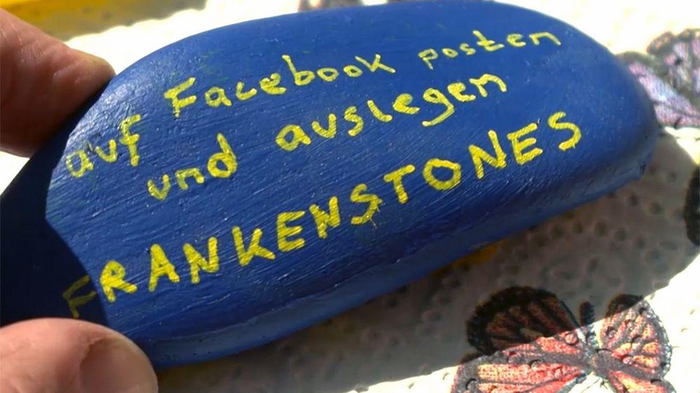 """""""Auf Facebook posten und auslegen - Frankenstones"""" steht auf einem blau angemalten Stein."""
