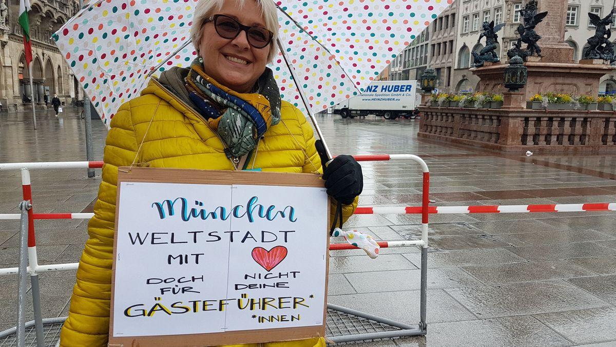 Gästeführerin demonstriert auf Münchner Marienplatz
