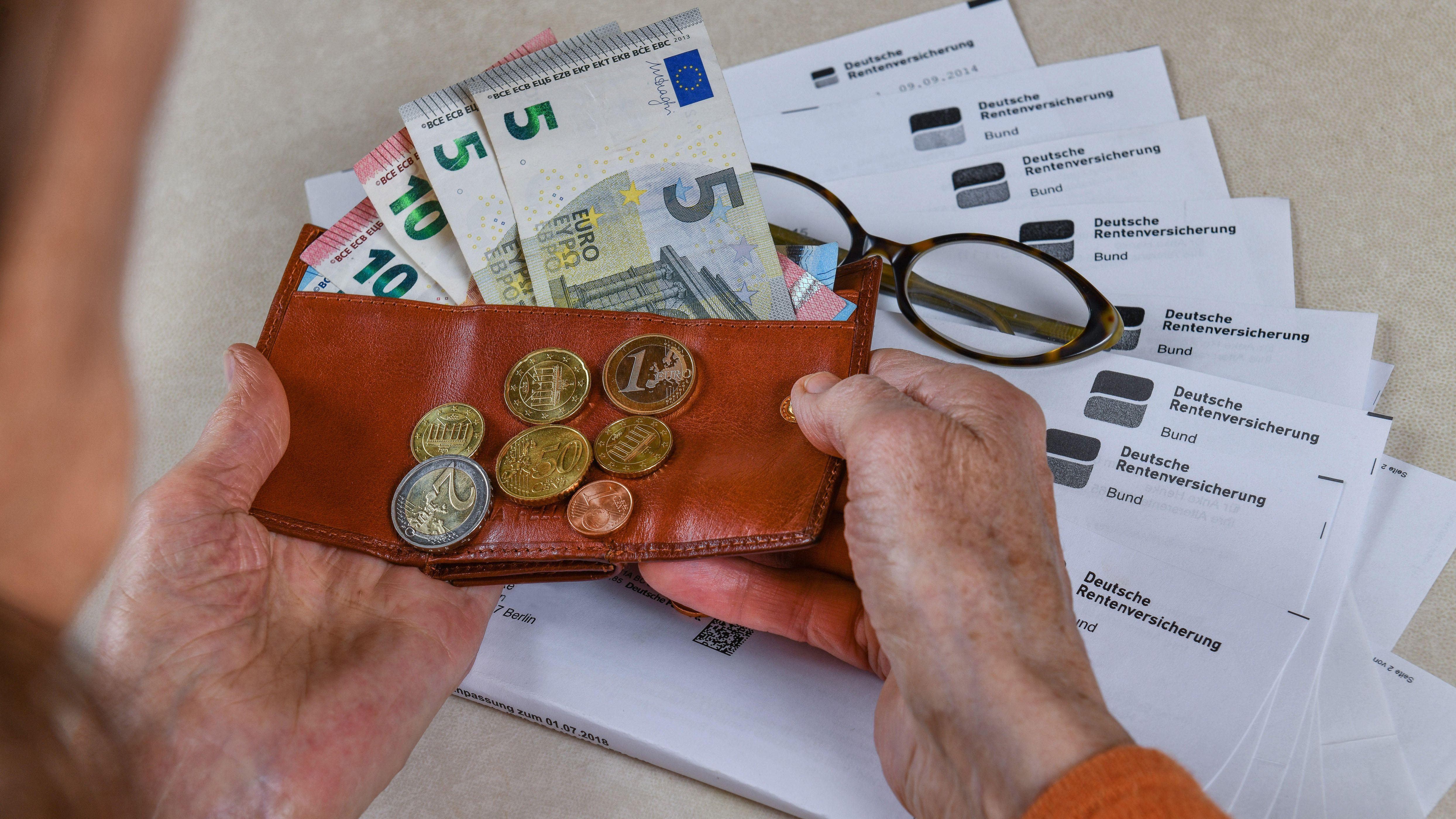 Eine ältere Frau hält ihren Geldbeutel in den Händen.