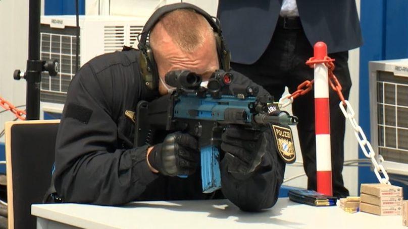 Ein Polizist in Uniform stützt sich auf einem Tisch auf und schießt mit einer Laser-Maschinenpistole