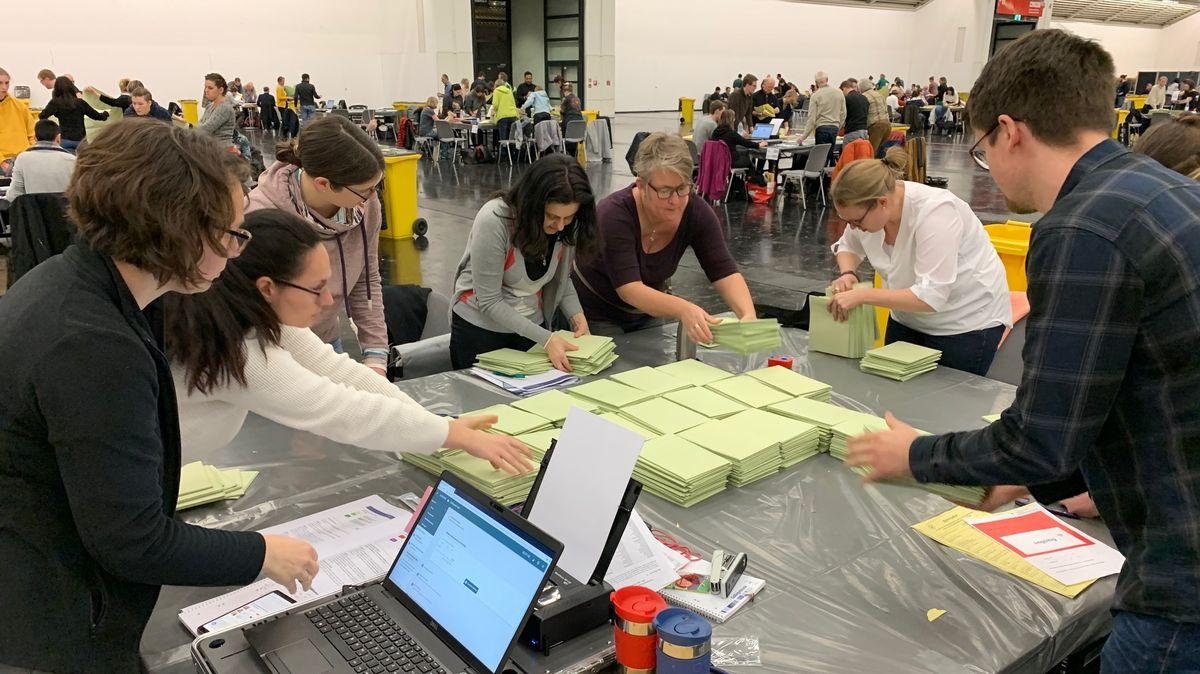 Wahlhelfer stehen in einer Halle der Messe München um einen Tisch mit Wahlunterlagen und zählen aus.