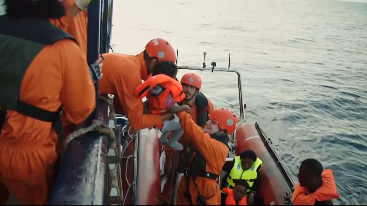 Helfer auf See heben ein kleines Kind von einem Schlauchboot auf ihr Schiff.