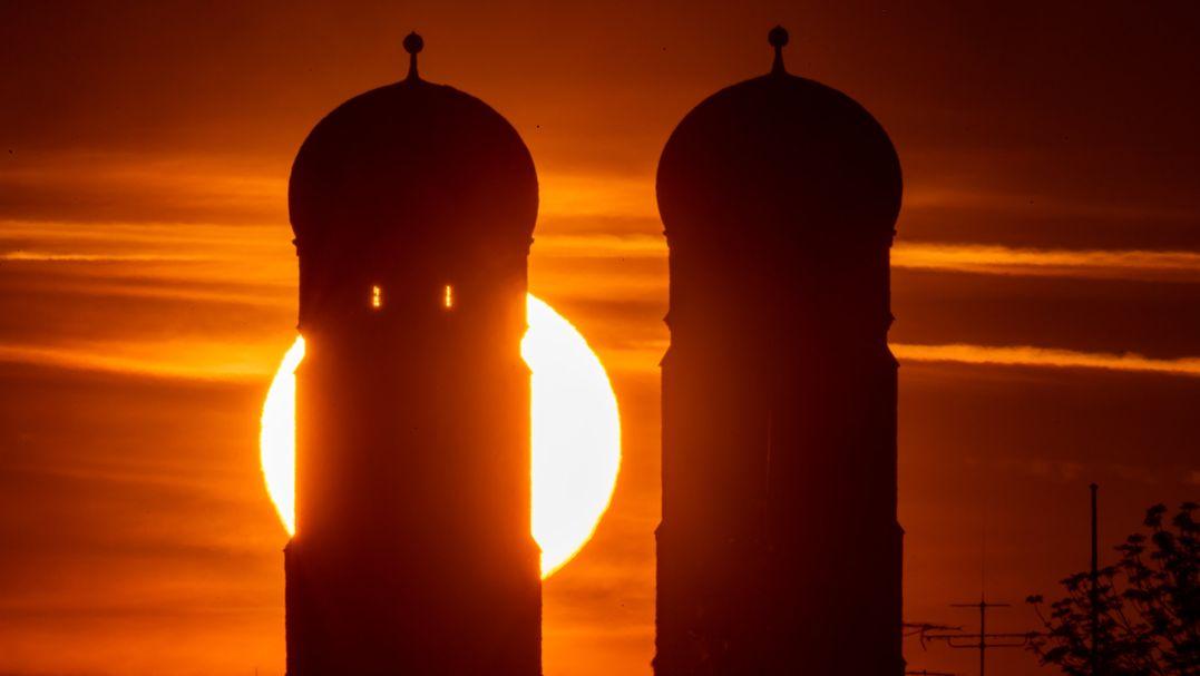 Die Sonne geht am Morgen zwischen den beiden 99 Meter hohen Türmen der Frauenkirche auf, die im Herzen der bayerischen Landeshauptstadt steht.