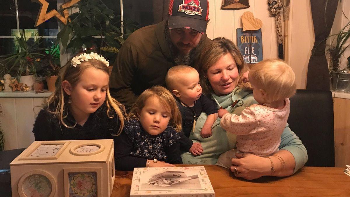"""Vater und Mutter und ihre vier kleinen Kinder betrachten eine Schachtel, auf der ein Foto eines tot geborenen Kindes zu sehen ist. Das Foto wurde vom Netzwerk """"Dein Sternenkind"""" gemacht, um bei der Trauer zu helfen."""