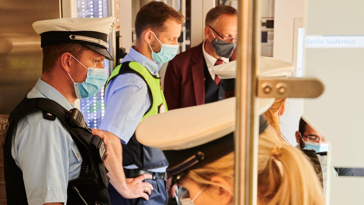 Drei Bundespolizisten mit Maske in einem Zug der Deutschen Bahn.