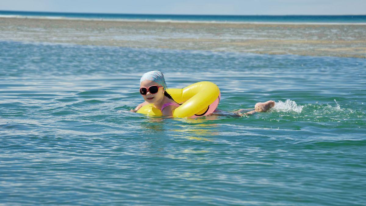 Kind mit Schwimmring im Meer