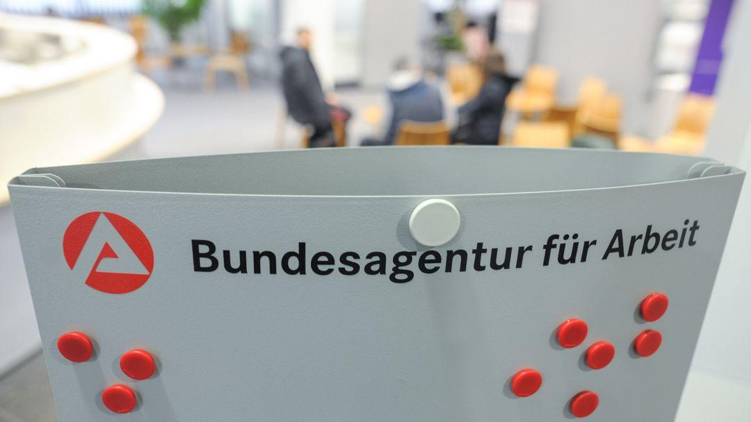 Drei Personen sitzen im Wartebereich der Bundesagentur für Arbeit hinter einem Aufsteller mit dem Logo der Agentur.