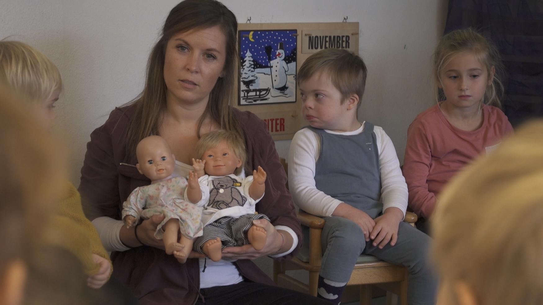 Erzieherin mit zwei verschiedenen Puppen im Arm