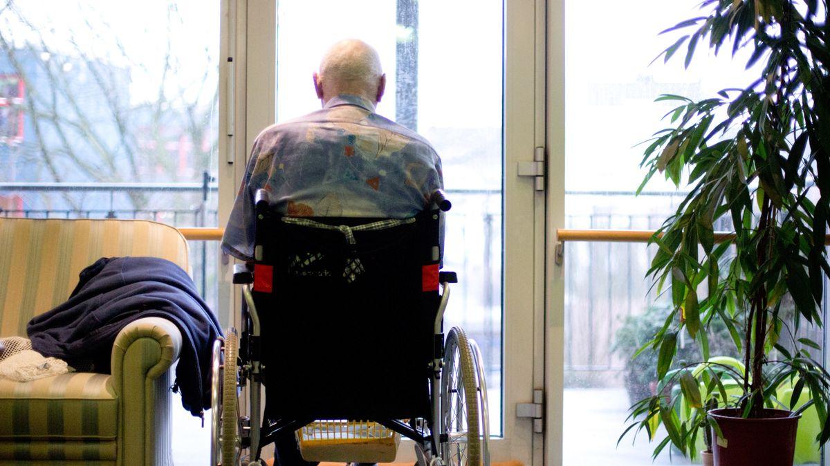 Bewohner eines Seniorenwohnheims sitzt im Rollstuhl am Fenster