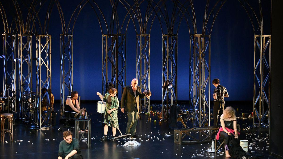 Sieben Schauspielerinnen und Schauspieler sitzen und stehen auf einer von metallenen Spalierbögen gesäumten, ansonsten aber weitgehend kargen und dunklen Bühne