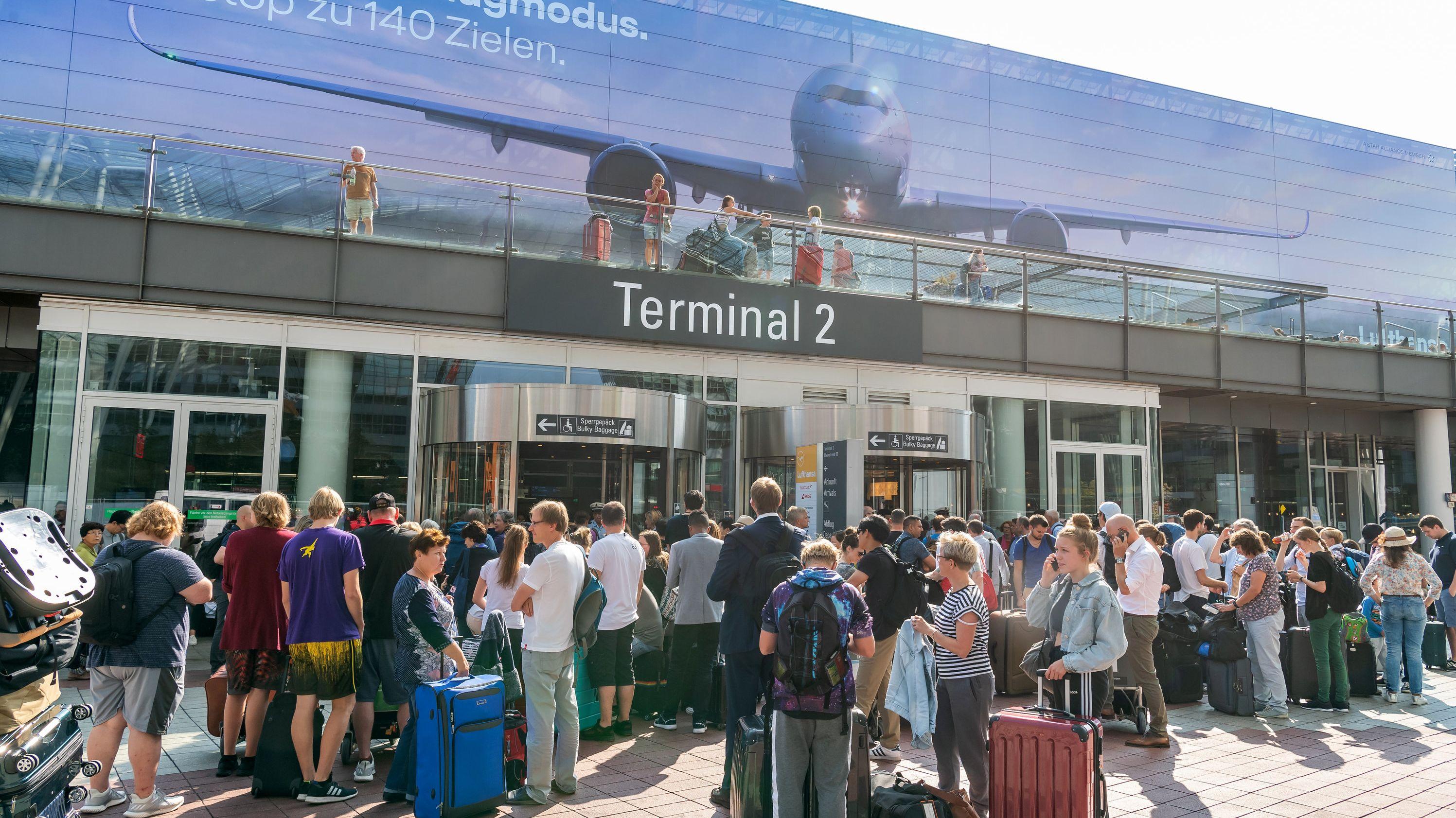Fluggäste stehen am 27. August vor dem verschlossenen Eingang zum Terminal 2 am Münchner Flughafen.
