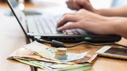Symbolbild: Euro-Scheine und -Münzen liegen vor einem Laptop | Bild:pa/dpa