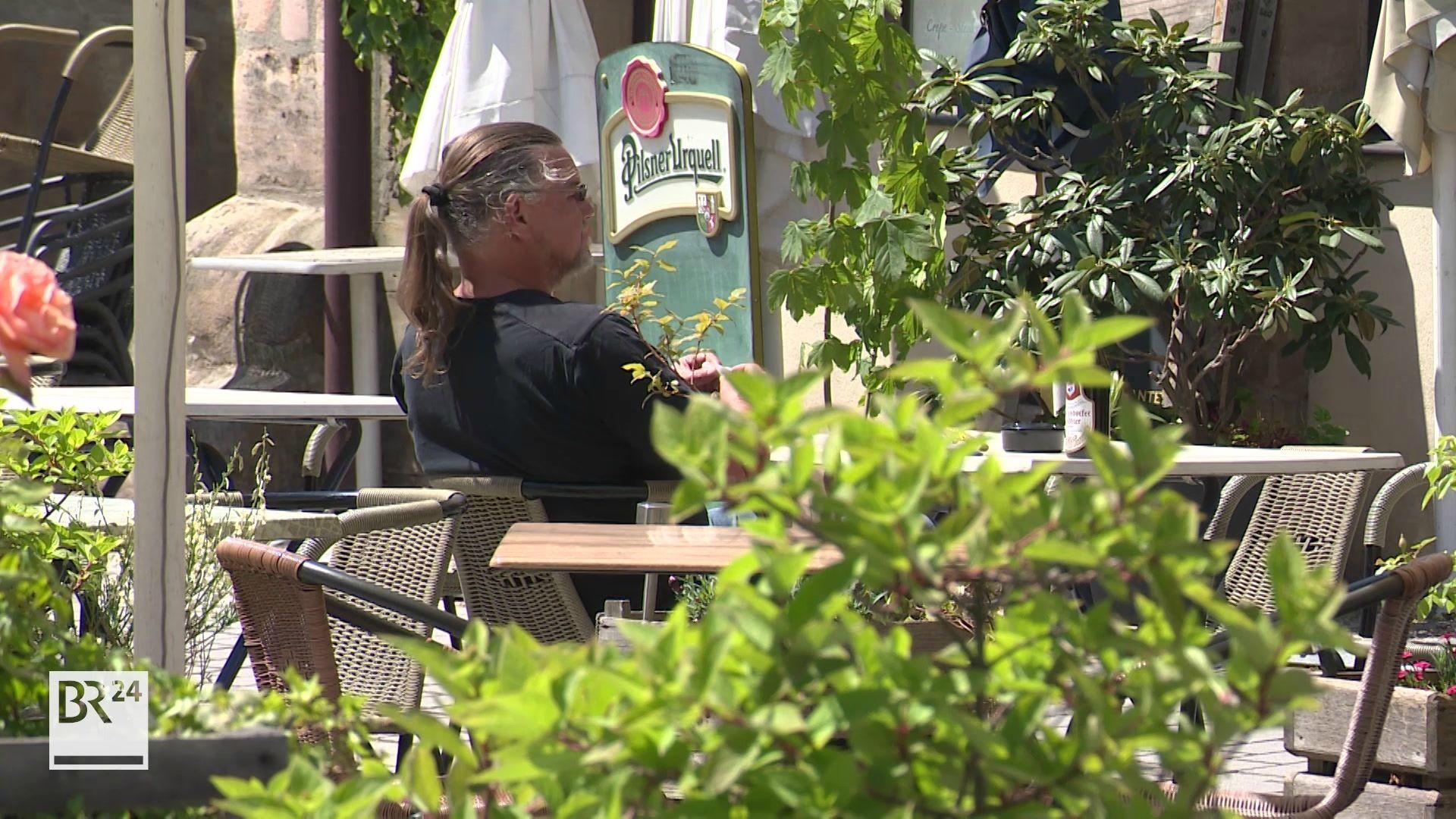 Mann an einem Tisch vor einem Lokal