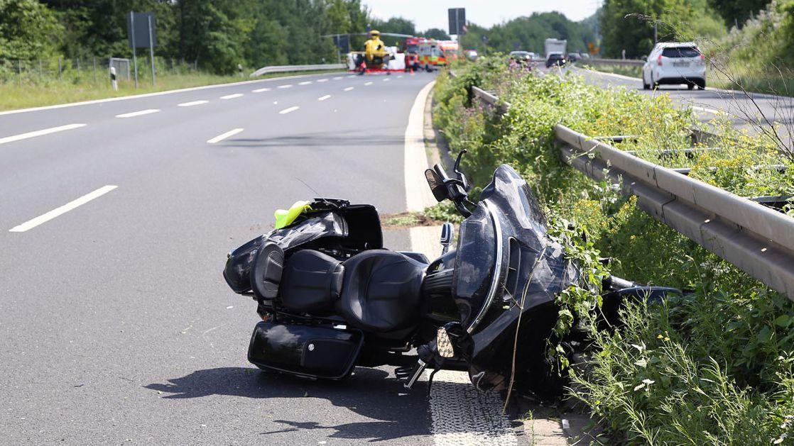 Umgestürztes Motorrad, im Hintergrund Rettungswagen und Rettungshubschrauber