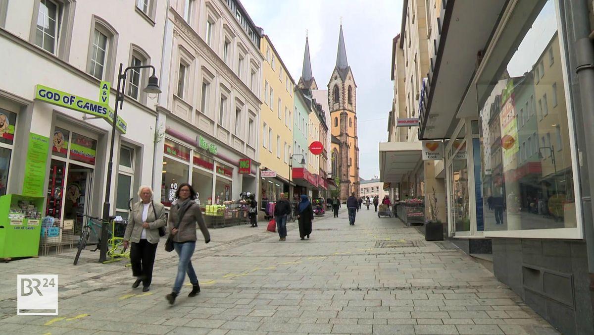 Passanten gehen durch die Fußgängerzone in Hof, dahinter die beiden Türme der Kirche.