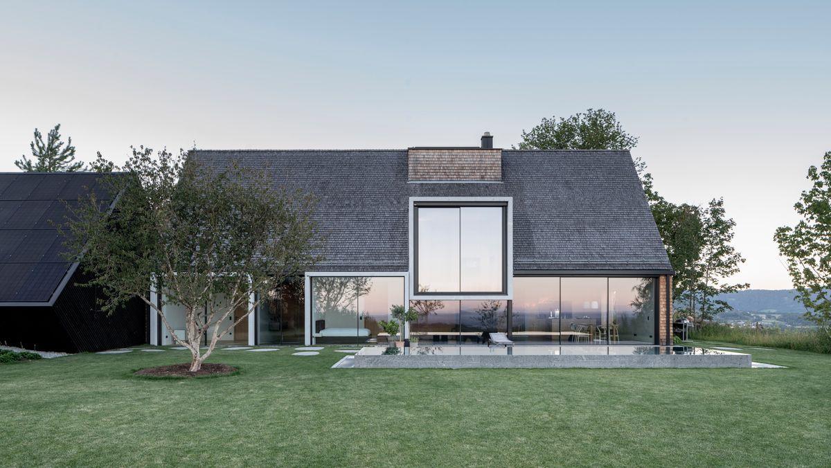 Seitenansicht des Hauses mit Rasen, Pool und großen Fenstern