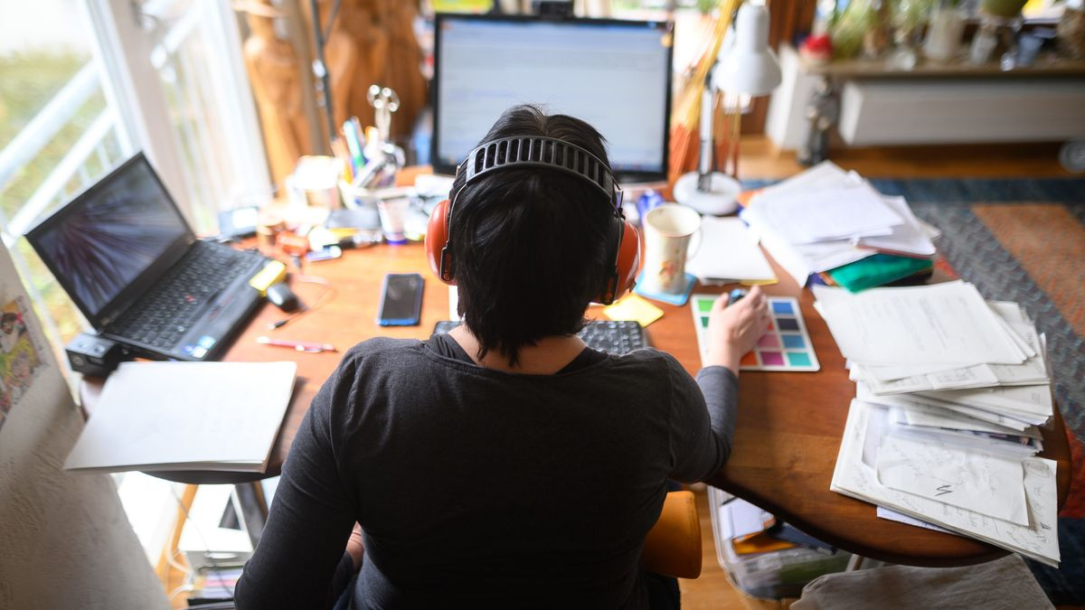 Eine Frau arbeitet mit Hörschutz im Homeoffice.