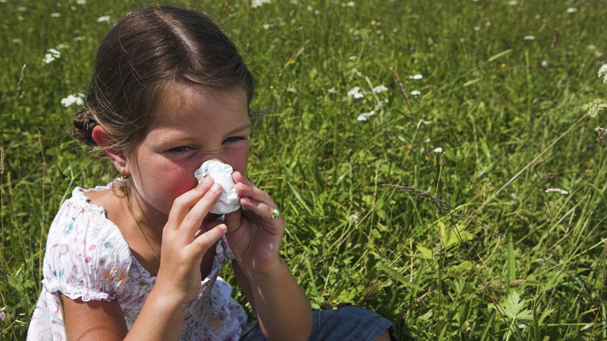 Kleines Mädchen schneuzt sich im Gras sitzend die Nase.