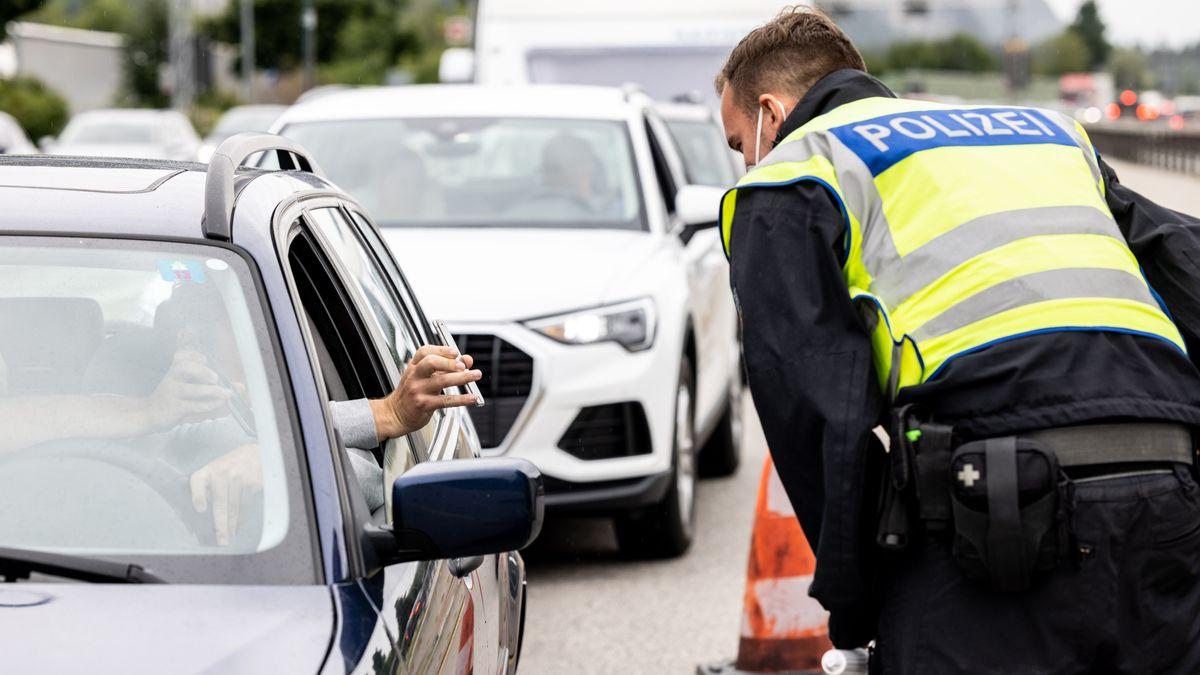 Autofahrer zeigt einem Bundespolizisten an der Grenze zu Österreich auf der Autobahn A93 digitalen Impfnachweis auf dem Smartphone.