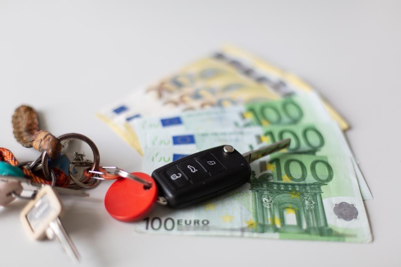 Ein Autoschlüssel auf mehreren aufgefächerten Geldscheinen.