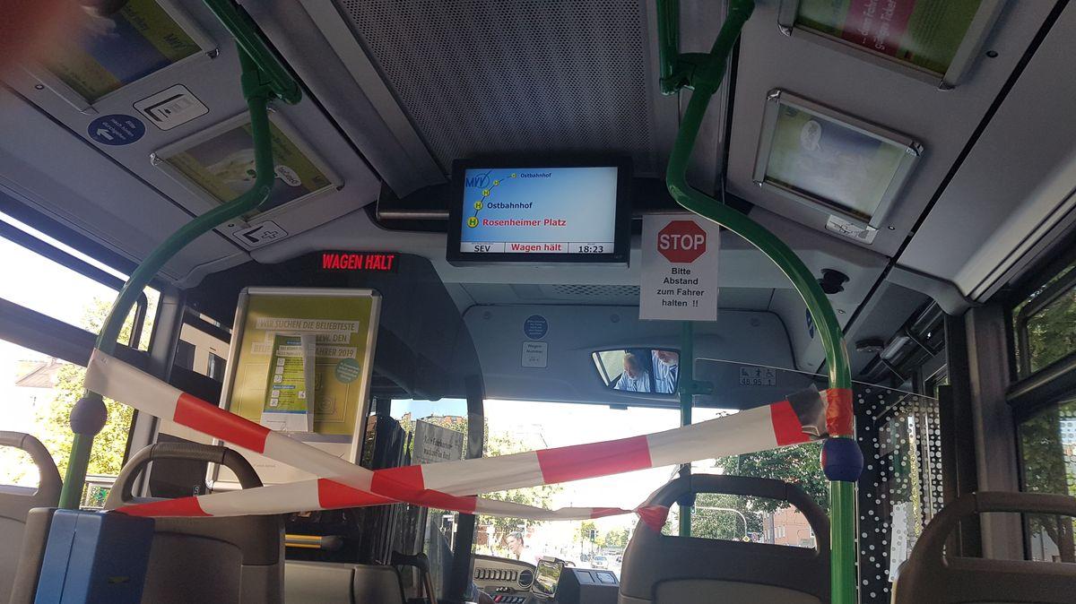 Ein rot-weißes Absperrband trennt den Busfahrer in einem Münchner Bus von den Fahrgästen.