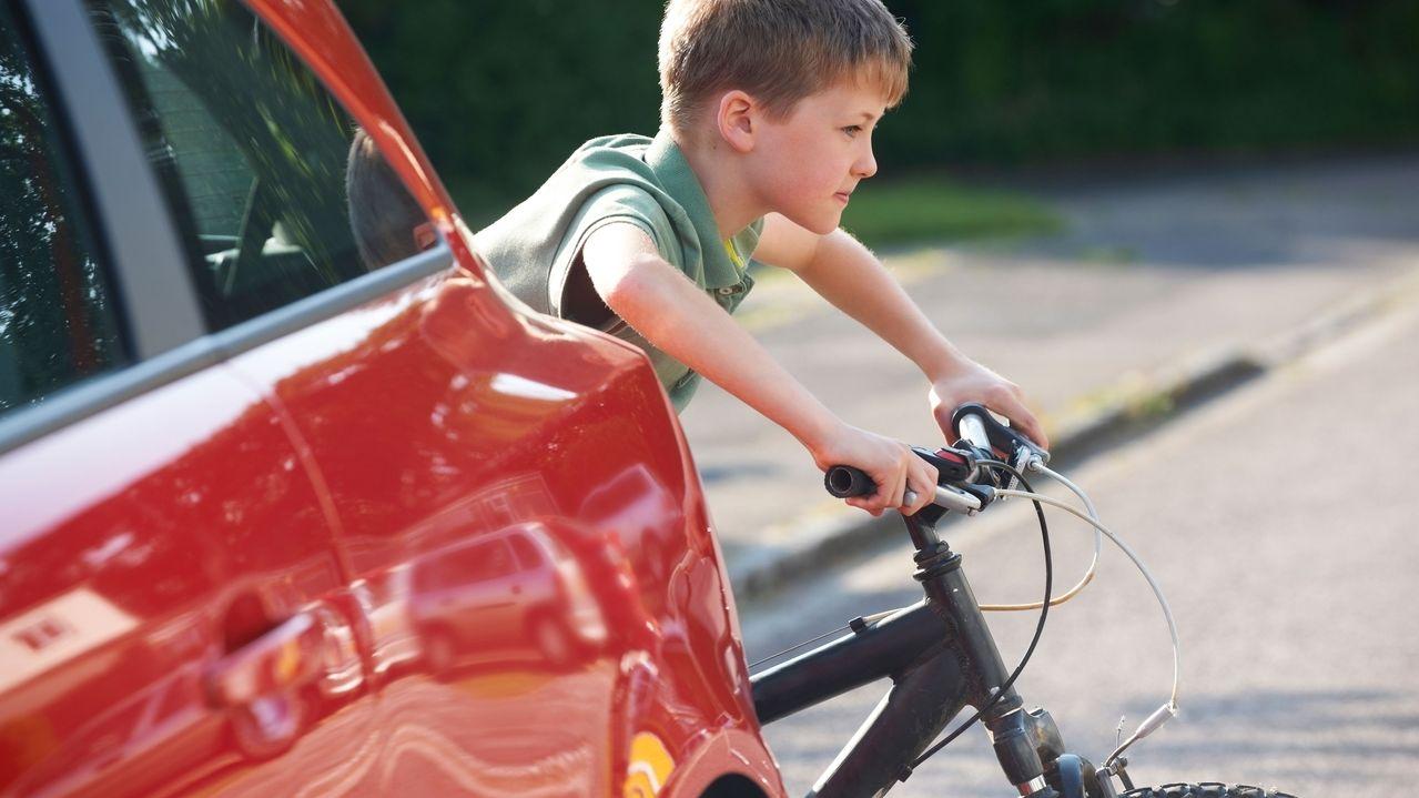 Junge mit Fahrrad überquert Straße hinter einem Auto (Symbolbild)