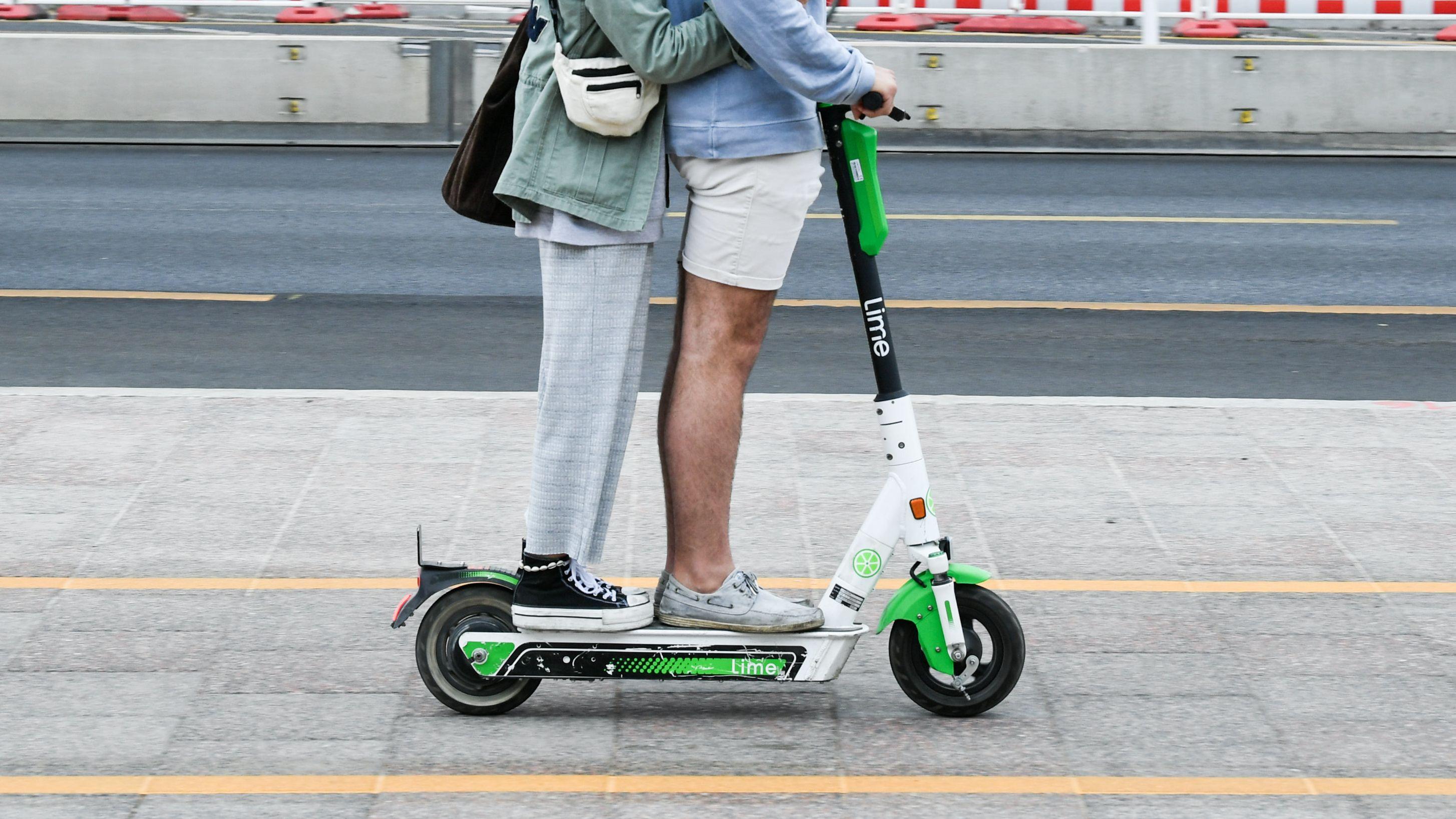 E-Scooter im Straßenverkehr: Zwei Personen fahren gemeinsam gleichzeitig auf einem E-Tretroller