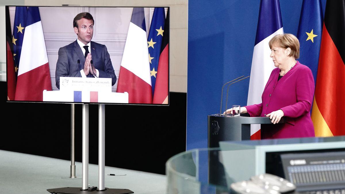 Merkel und Macron in einer Pressekonferenz per Videoschaltung - Merkel im Raum, Macron auf dem Bildschirm.
